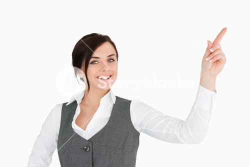 Smiling welldressed brunette pointing up