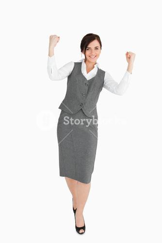 Woman in grey suit walking the fists raised