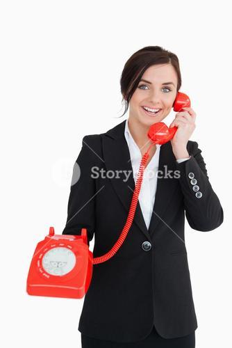 Businesswoman holding an old red phone