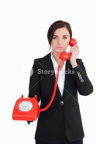 Business woman using a red dial telephone