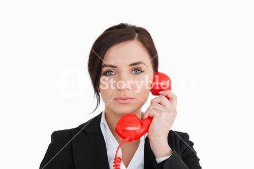 Attractive woman in suit using a red dial telephone