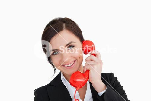 Smiling woman in suit using a red dial telephone