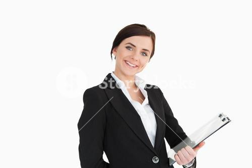Woman in suit smiling while holding a clipboard