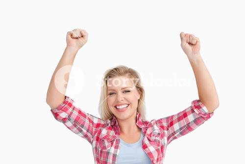 Cheerful blonde woman raising her two fists