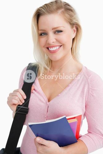 Smiling young woman holding school books