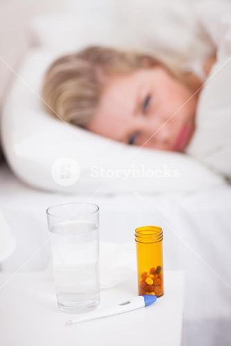 Medicines and thermometer on a beside table
