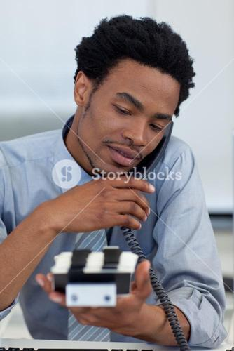 Young businessman on phone looking at card holder