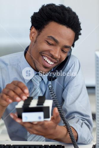 Smiling businessman on phone looking at card holder