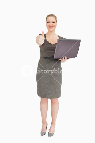 Woman holding a laptop while she is thump up