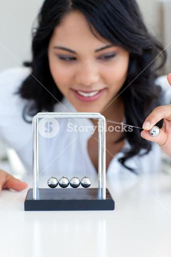 Businesswoman playing with Newton balls