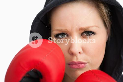 Woman protecting her face with boxing gloves