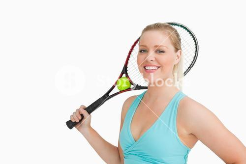 Smiling woman holding a tennis raquet and ball