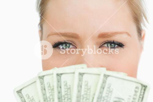 Close up of a woman face hidden with dollars banknotes