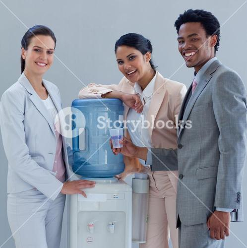 Smiling business people with a water cooler in office