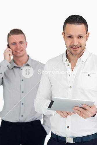 Two smiling men using phone and tablet computer