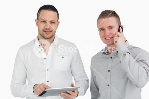 Two smiling men with a phone and a tablet computer