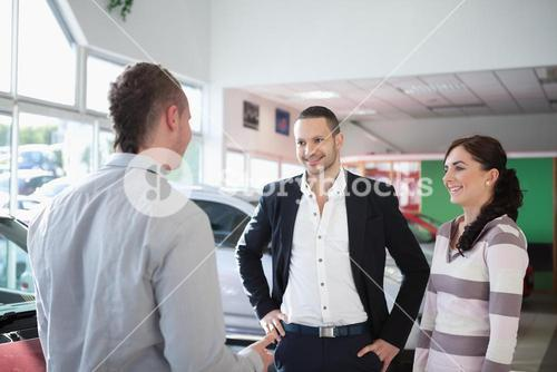 Car dealer chatting with a couple
