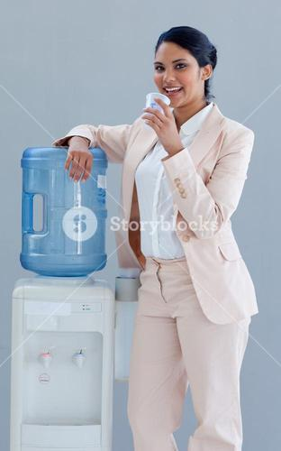 Businesswoman drinking from a water cooler