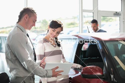 Smiling woman chatting with a car dealer