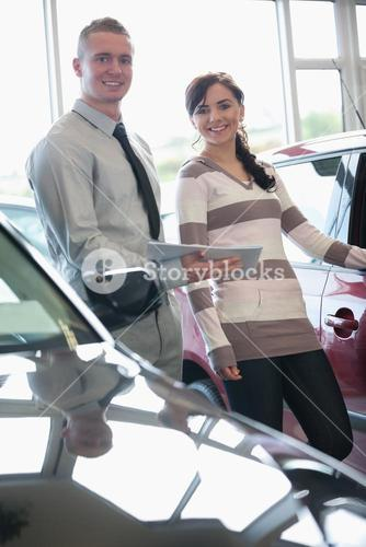 Salesman and a woman standing next to a car