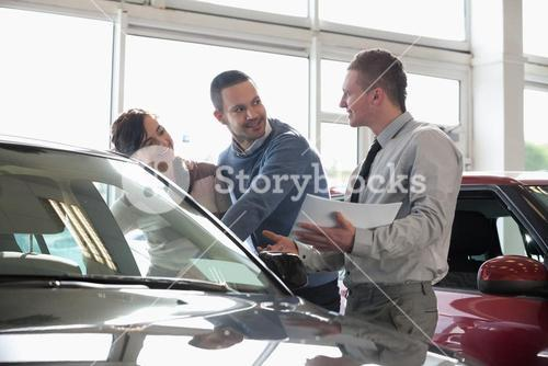 Salesman and a couple looking at a car