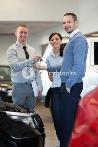 Smiling salesman handing keys to a happy couple