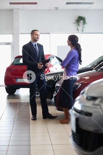 Salesman and a woman talking next to a car