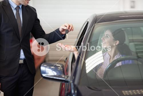 Smiling woman in a car taking keys