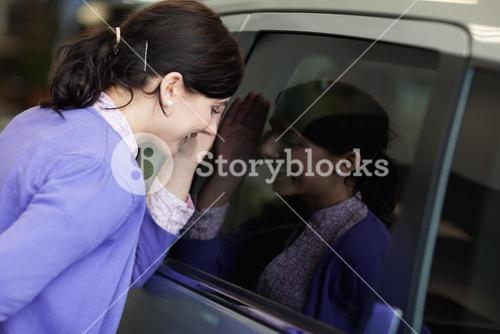 Woman looking inside a car