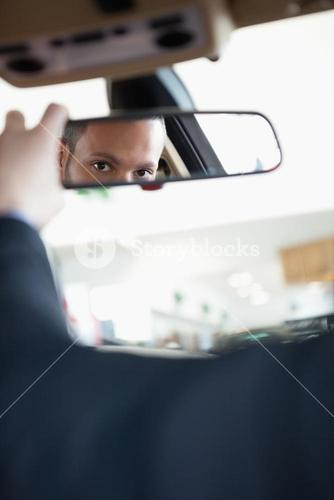 Man adjusting a rear view mirror