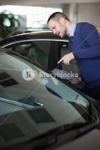 Man looking inside a car