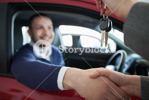 Woman giving car keys while shaking hand