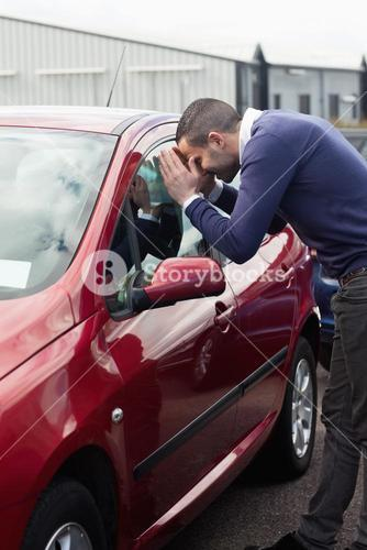 Man looking through the window of the car