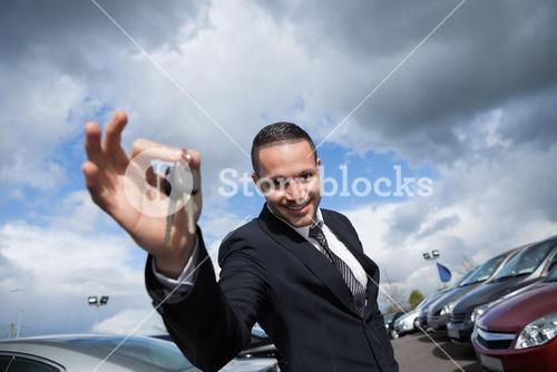Happy seller holding car keys