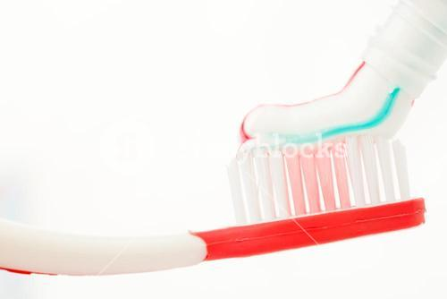 Red toothbrush with multicolour toothpaste