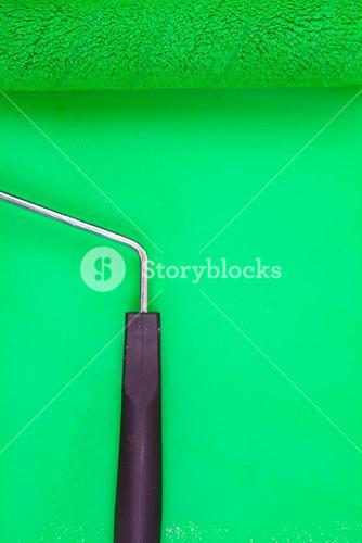 Green paint roller on a background
