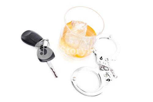 Tumbler glass with whiskey with car key and handcuff