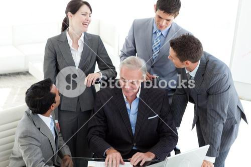 Laughing business team looking at a document with their manager
