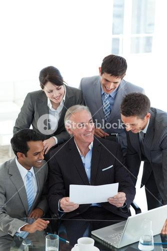 Senior manager showing sales report to his colleagues