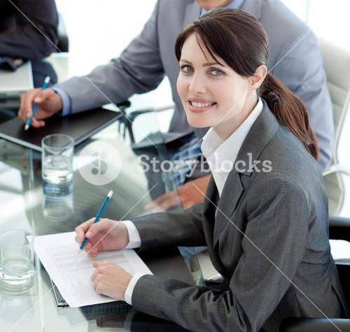 Smiling businesswoman studying a document in a meeting