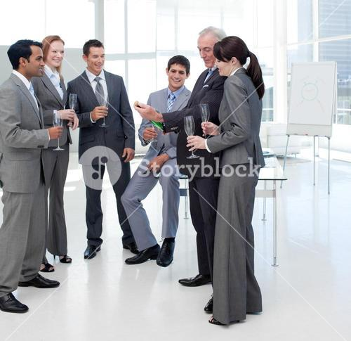 Successful business people looking at a bottle of Champagne