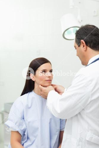 Doctor touching the neck of a patient