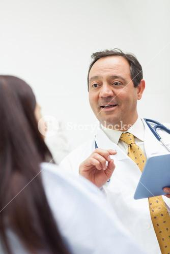 Smiling doctor talking with a patient while holding a tablet