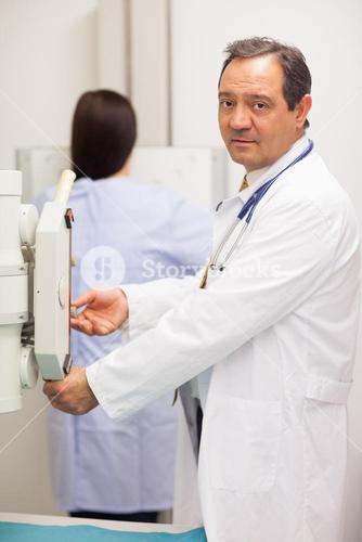 Doctor checking a machine while a patient is having a mammography