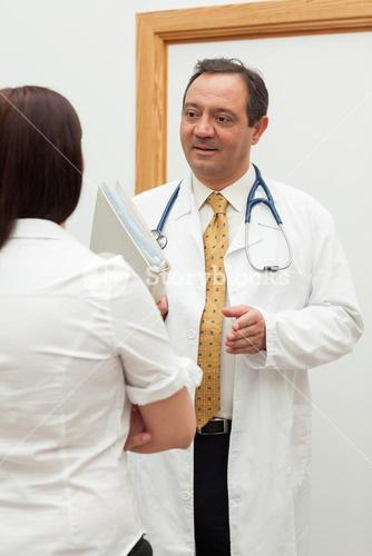 Doctor holding files while talking to a patient