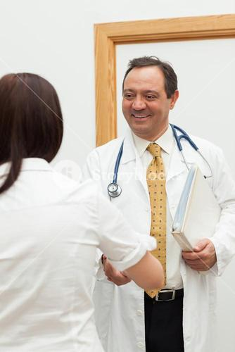 Doctor shaking the hand of a patient while holding a file