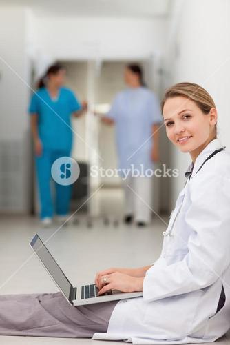Woman doctor sitting on the floor while typing on a laptop