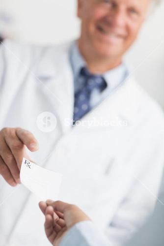 Customer handing a Rx prescription to a pharmacist