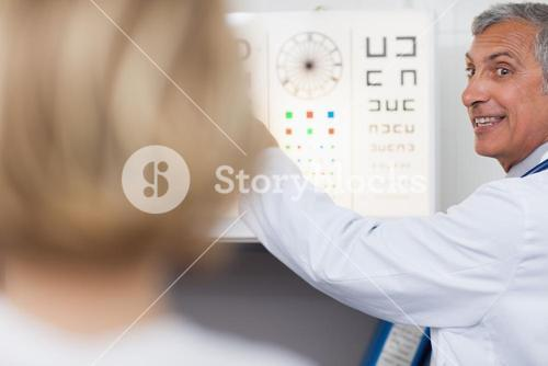 Smiling doctor doing an eye test on a patient in a hospital