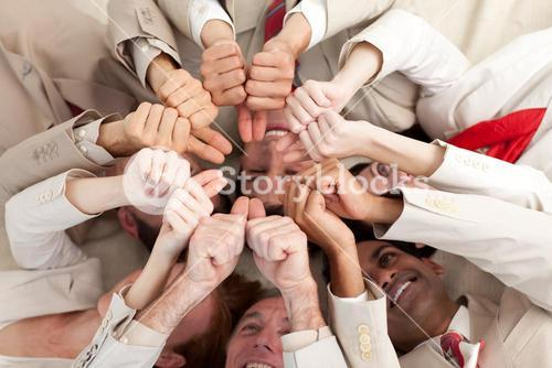 Successful business team with thumbs up lying in a circle